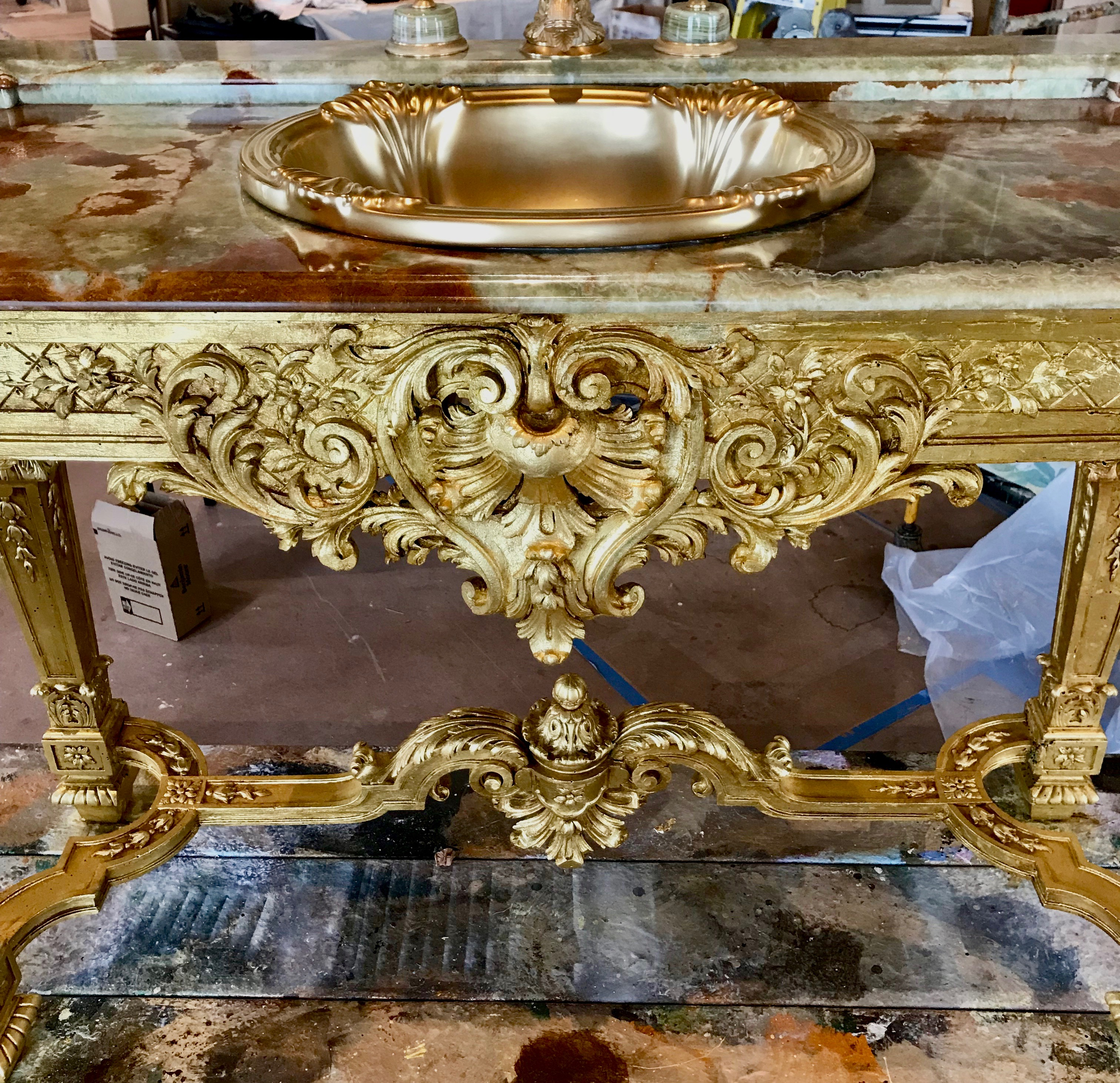 A picture of a bathroom vanity that was gilded with 24k gold by Mabel Vittini.