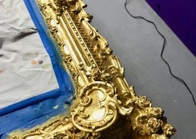 gilding: Gold leaf application to mirror frame