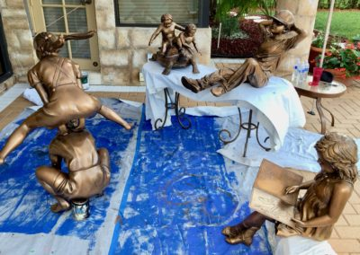 Four Exterior statues of children playing after being refinished by Vitti Art Decor & Painting.