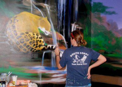 Mabel Vittini painting a Jaguar in Custom Rainforest Mural
